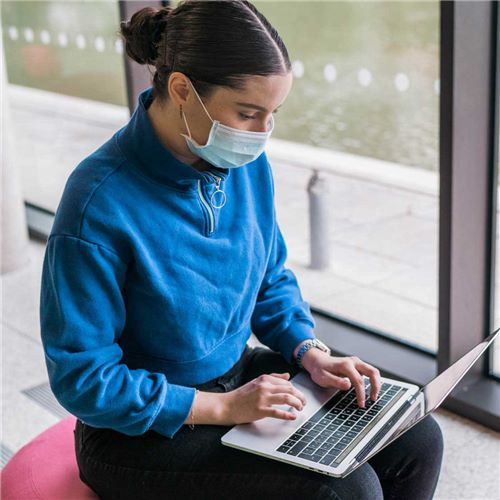 Student wearing a facemask using a laptop